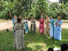 The Shanti Uganda doula trainees sing and dance with traditional  birth attendant Florence.  They are wearing gomesi, the traditional Ugandan dress.